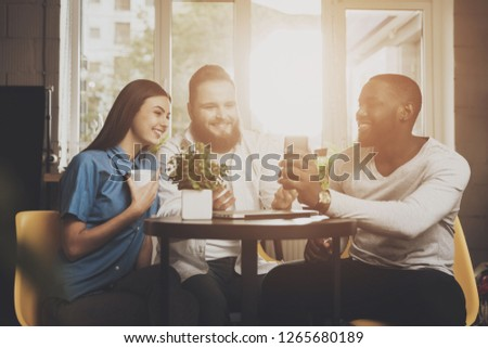 A company of friends sits in a cafe at the table. Afro American man showing photos on a mobile phone to his young friends sitting in a cafe behind the floor. The concept of multiethnic friendship.