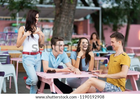 A company of good-looking friends is laughing, socialising and sitting at the table in the nice summer cafe. Entertainment, having good time. Friendship. #1190192908