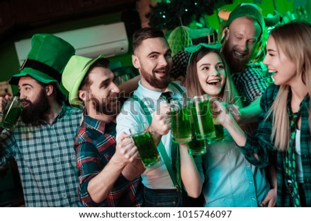 A company of young people is resting in a beer bar. They celebrate St. Patrick's Day. They are having fun.