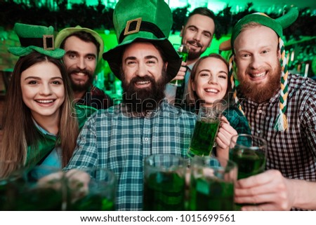 A company of young people posing on the camera with glasses of beer in their hands. They celebrate St. Patrick's Day at the pub. They are very fun.