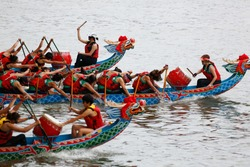 A competitive racing on Keelung River, where the women athletes pull vigorously on the oars to the pace of the drumbeats by the team leaders, in the traditional Dragon Boat Festival in Taipei, Taiwan