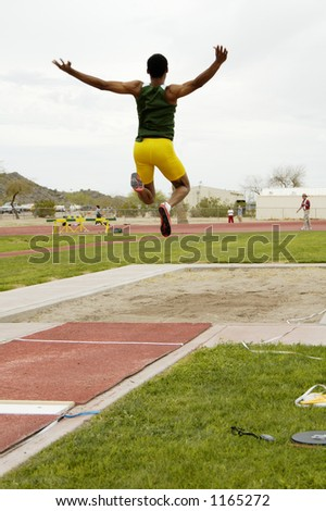 A competitor in the men's long jump event during a college track meet.