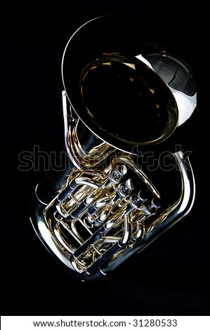 A complete brass gold bass tuba euphonium against a black background in the vertical format with copy space.