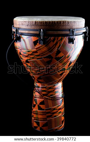 A complete orange African or Latin Djembe conga drum isolated on black background in the vertical format.