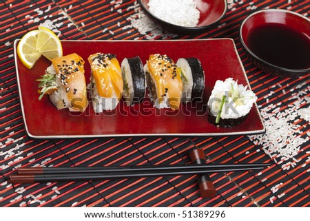 A complete sushi meal with chopsticks on tatami mat.