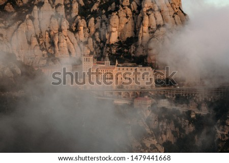 A complex of buildings set in steep rocks partially hidden in the clouds #1479441668