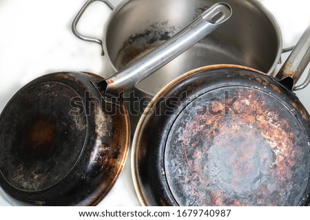 A composition of burnt and dirty, stainless steel pots and pans on a white background. Isolated. Foto stock ©