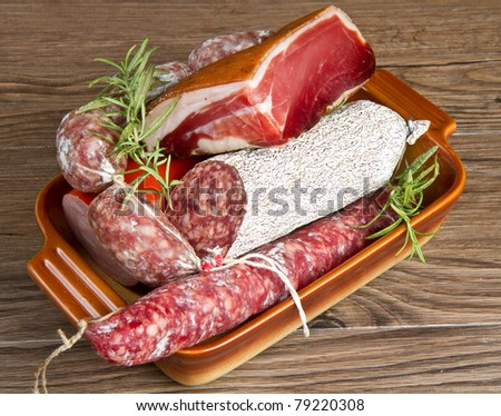 A composition of different sorts of cold cuts on wooden table