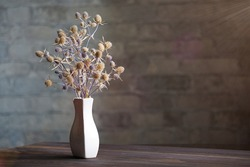 A composition of dried flowers in a white porcelain vase on a wooden table. Space for text, space for copying.