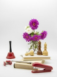 A composition of flowers in a vase, books and various educational accessories on a light background. Congratulations on the teacher's day.