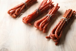 A composition of homemade, smoked kabanosy tied with string, on light wooden boards, top view. Traditional, thin, dry Polish pork, beef sausages. Meat delicacies, snacks, cold cuts.