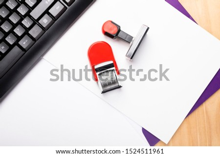 A composition of office accessories. A red rubber stamp and date stamp, paper file and keyboard on a wooden desk.  #1524511961