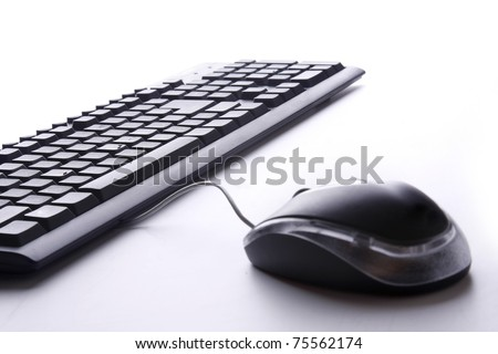 A computer keyboard with a mouse isolated on white
