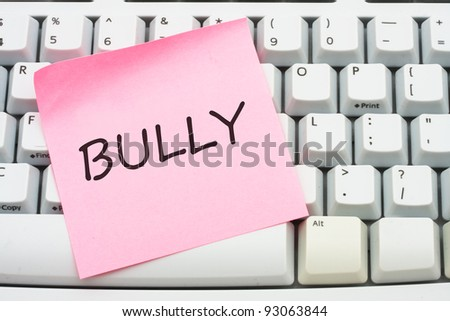 A computer keyboard with a sticky note saying bully, Internet bullying
