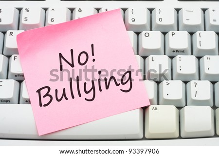 A computer keyboard with a sticky note saying no bulling, Stop internet bullying