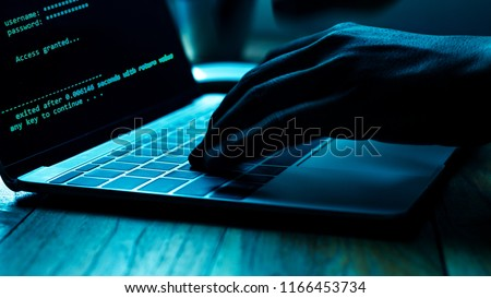 A computer programmer or hacker prints a code on a laptop keyboard to break into a secret organization system.