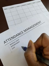 A concept image for attendance management showing a Black person tracking different types of absences with a calendar