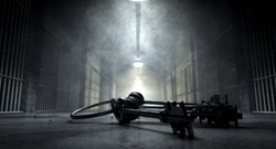 A concept image of an eerie corridor in a prison at night showing jail cells dimly illuminated by various ominous lights and a bunch of cell keys laying ominously on the floor