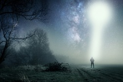 A concept of a UFO above a lone hooded figure with a light beam coming down. Standing on a path on a spooky misty night, with a cold grainy blue edit.