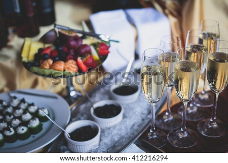 A concept of luxury wealthy life symbol with sparkling champagne in glass and black caviar with ice on a catering table