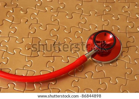 A concept of networked healthcare using a stethoscope and a jigsaw puzzle. - stock photo