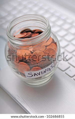 a concept of working a lot to save a little bit of money which is signified by a computer keyboard and pennies in a jar