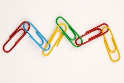 A concept photo of a wavy link of multi-colored paperclips.