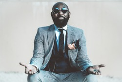 A concept photo with an elegant bald bearded black man in a suit with tie and round sunglasses from the matrix offering to make a choice with red and blue pills in his hands