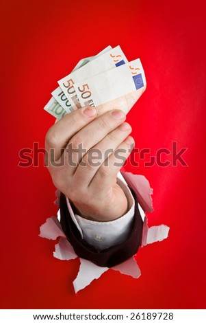 A concept photograph of a hand (shirt sleeve and jacket visible) bursting through a red paper wall. The hand is gripping some 100 and 50 Euro bills.