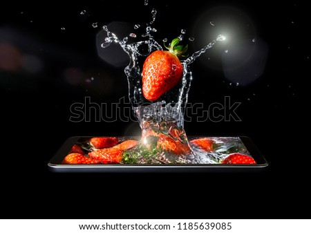 A conceptual creative 3D volumetric photo of a ripe red strawberry close-up in splashes of water and sunlight falling into the water in a smartphone isolated on a black background.