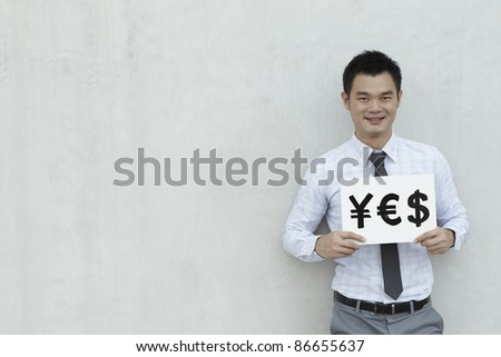 A conceptual image about choice. The Asian man is holding & sign with the $, Yen & Euro symbols.