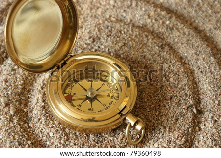 A conceptual image demonstrating a compass and it's magnet field using rings in the sand.