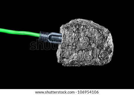 A conceptual image of an extension cord plugged into a chunk of bituminous coal isolated on black.