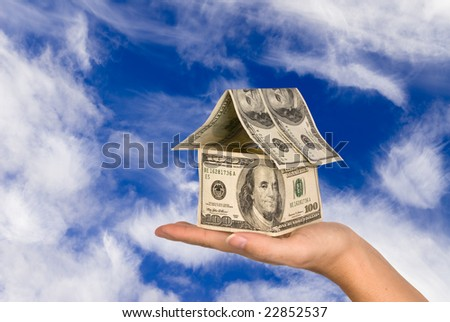 A conceptual real estate and economic inference image showing a one hundred dollar bill house being held in the palm of ones hand against a beautiful sky.