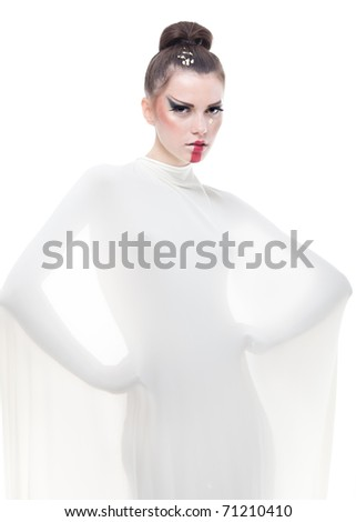 a conceptual studio image of a young woman dressed in a white stretch fabric and wearing vanguardist makeup. - stock photo