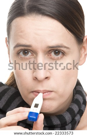 A concerned woman taking a temperature reading with a thermometer - stock photo