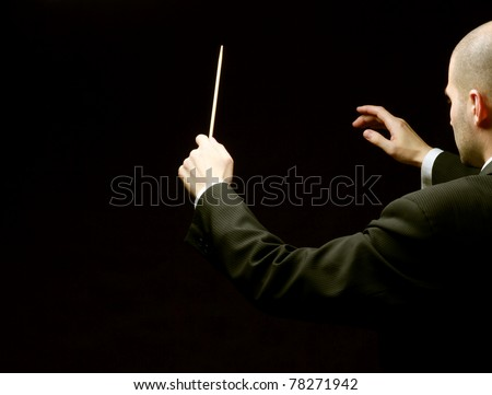 A concert conductor with a baton isolated on a black background, back-view