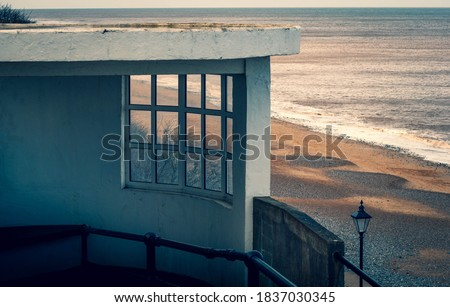 A concrete and glass lookout shelter overlooking the sandy beach at Cromer in Norfolk, UK Foto stock ©
