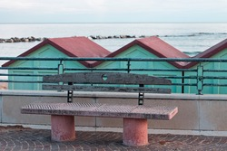 A concrete and wooden bench on the sidewalk in front of beach cabins on the Mediterranean coast (Pesaro, Italy, Europe)
