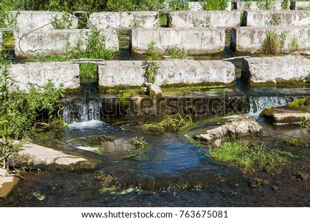 A concrete blocks lying on a small river - dam #763675081