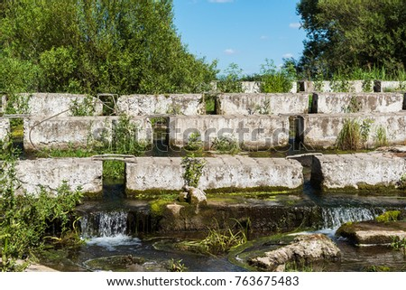 A concrete blocks lying on a small river - dam #763675483