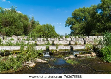 A concrete blocks lying on a small river - dam #763675588