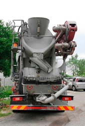 A concrete mixer truck delivering concrete to a domestic building site in Udine, NE Italy. Such vehicles use a revolving drum to mix the ingredients and are able to supply ready-mixed concrete on site