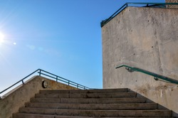 A concrete set of stairs with wall and attached safety railings lead up to blue sky and the glare of the sun.