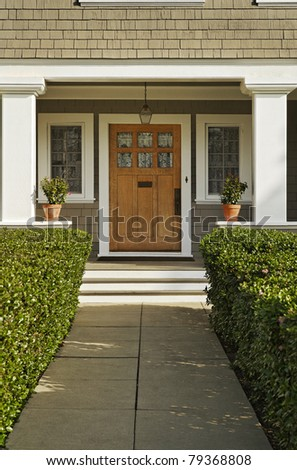 A concrete walkway bordered with hedged shrubs leads to the front door of a home. There are windows on either side of the door. Vertical shot.