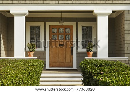 A concrete walkway bordered with hedged shrubs leads to the front door of a home. There are windows on either side of the door. Horizontal shot. - stock photo