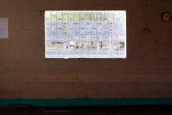 A concrete wall with a bright grated window at the center