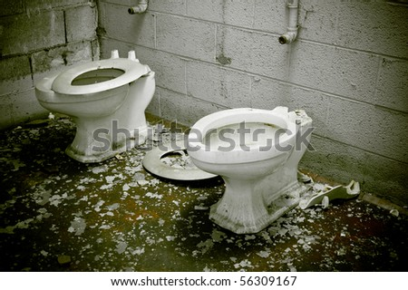 A condemned bathroom with dirty toilets in an abandoned warehouse factory.