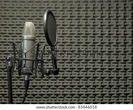 A condenser microphone with shock mount and pop shield inside an acoustic booth with acoustic panels on the background - stock photo