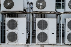 A condensing unit is a component of split type air conditioners, which is used to cool the heat generated by compressing the air of the compressor.on white wall.
